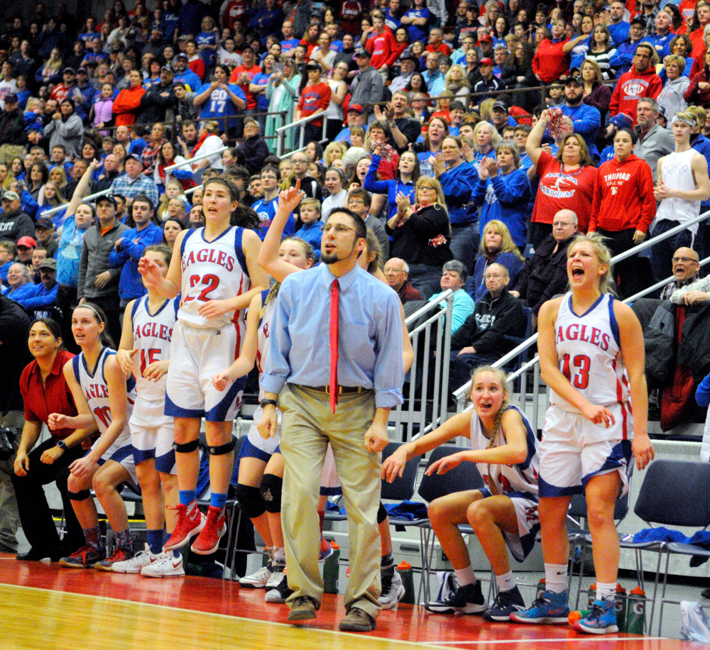 Messalonskee's bench and fans celebrate a basket in the final minutes against Brunswick in the Class A state championship Saturday at the Augusta Civic Center.