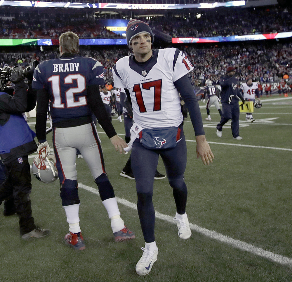 In this Jan. 14 photo, New England quarterback Tom Brady (12) and Houston quarterback Brock Osweiler (17) pass at midfield after a divisional playoff game in Foxborough, Massachusetts. The best quarterbacks never become free agents, of course, but Osweiler brought enough intrigue and promise with his 6-foot-7 frame after playing behind Peyton Manning in Denver that Houston doled out $37 million guaranteed on a four-year contract for the backup on the Broncos about a month after they won the Super Bowl.