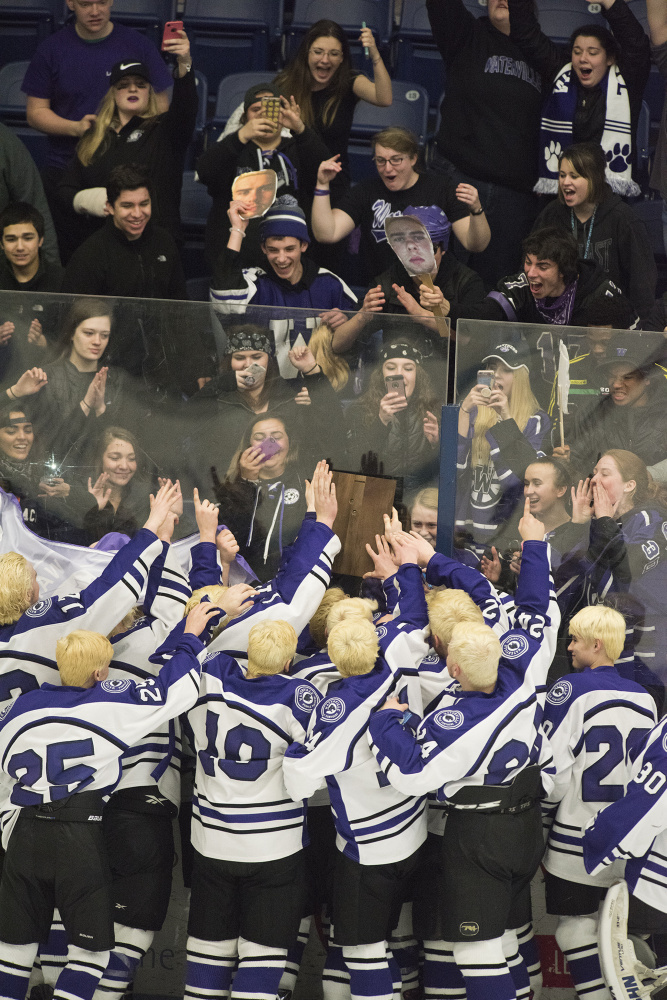 The Waterville hockey team celebrates after they won the Class B North championship with a 6-5 overtime victory over Old Town/Orono on Tuesday night in Orono.