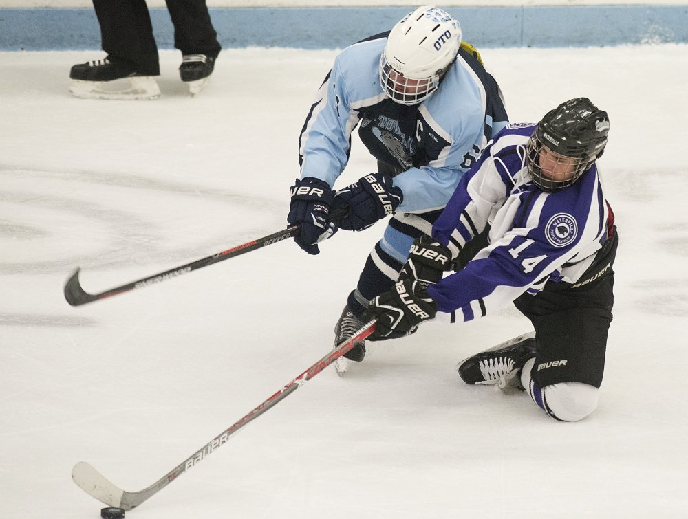 Old Town/Orono's Austin Sheehan and Waterville's Michael Bolduc battle for the puck during the Class B North regional championship Tuesday in Orono. The Purple Panthers play York at 1 p.m., today for the Class B state championship.
