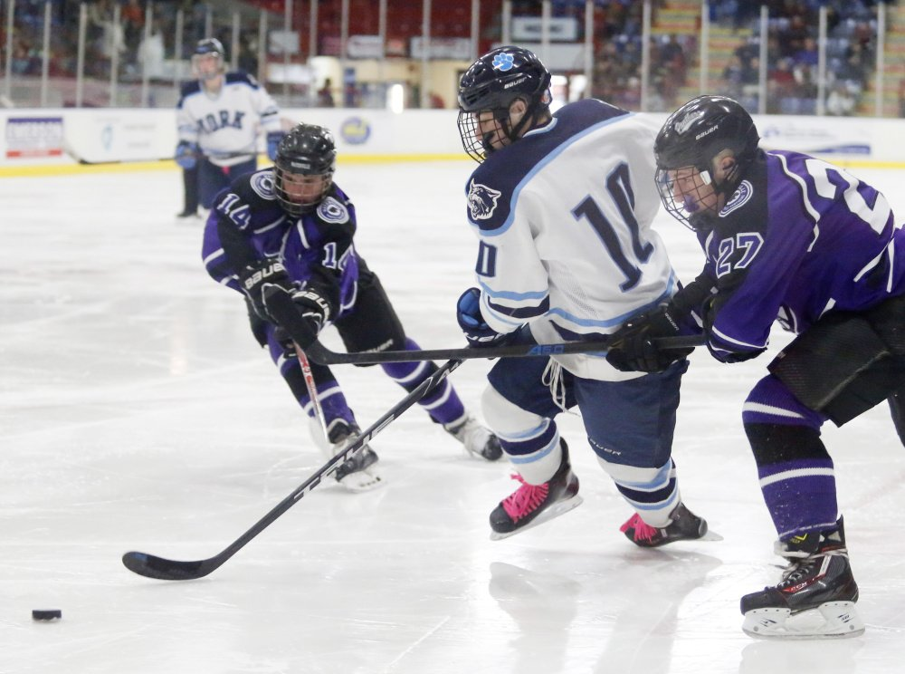 Dalton McCann of York skates between Waterville's Michael Bolduc, left, and Chase Wheeler in the second period of the Class B state championship game Saturday at the Androscoggin Bank Colisee in Lewiston.