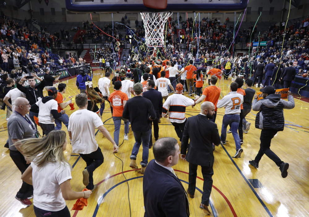 Princeton fans storm the court following the Ivy League championship game against Yale on Sunday.