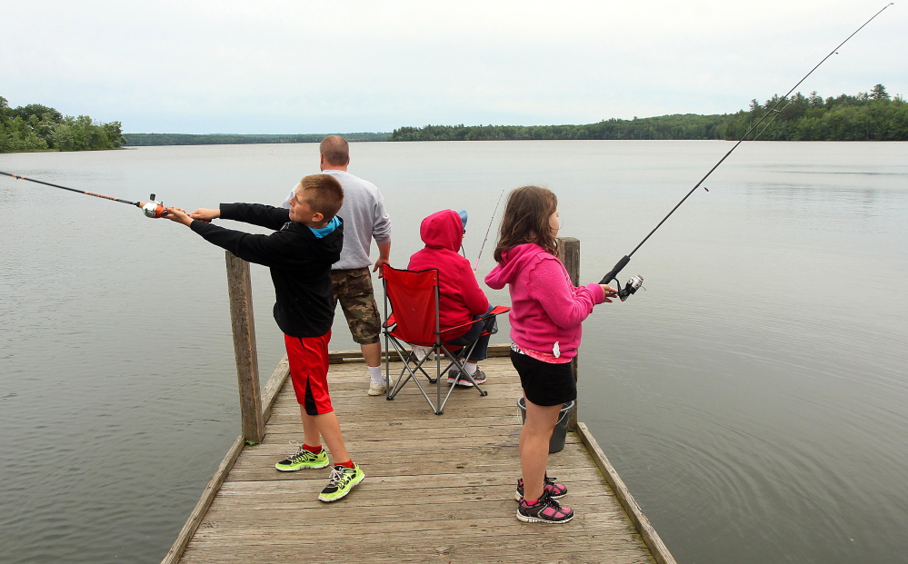 A Waterville family fishes in 2014 on China Lake in East Vassalboro. The Kennebec Water District, which owns the west basin shorefront there and draws its water supply from the lake for 30,000 customers, opposed recent legislation that aimed to charge district users $5 per year to help improve the lake's water quality. A legislative committee voted March 2 that the bill ought not to pass.