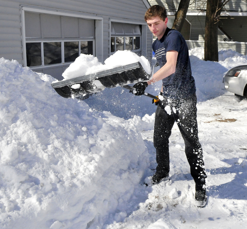 "Kyle Howard needed to wear only a T-shirt while shoveling snow Wednesday. ""It got so warm today I took off my coat,"" Howard said."