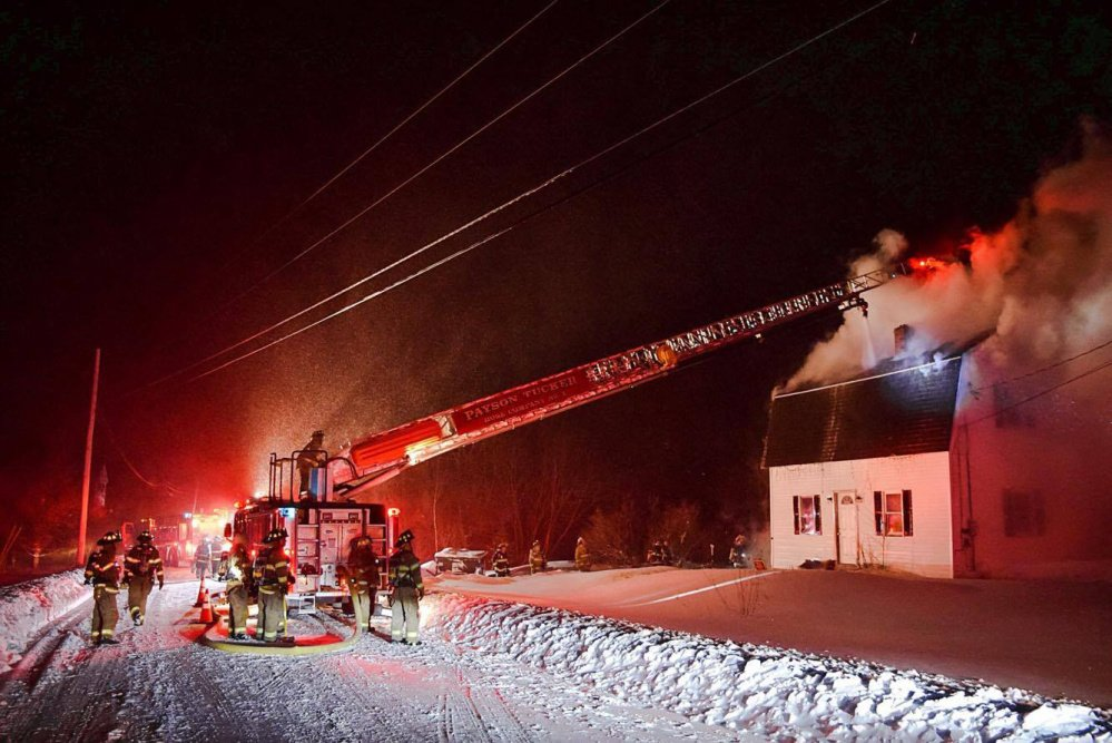 Winthrop Fire Department's truck 3 shoots a stream of water Tuesday into the attic through an opening in the roof of a home on Route 135 in Monmouth. The home may be total loss.