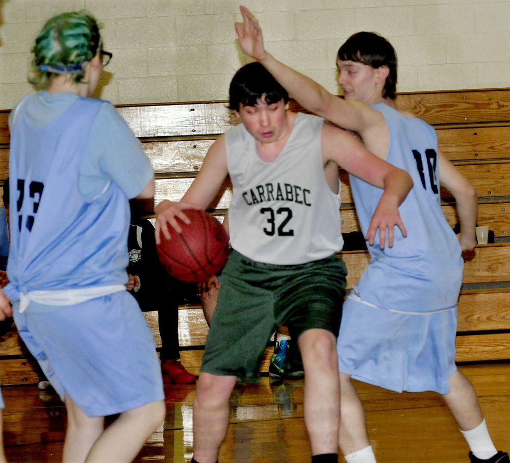 Carrabec/Madison's Roger Pickard drives between two Oceanside defenders during a unified basketball North quarterfinal Wednesday afternoon in North Anson.