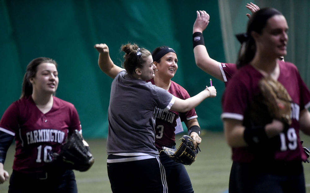 University of Maine Farmington center fielder Kiana Thompson (13), right center, celebrates with teammates after beating the University of Miane at Presque Isle on Saturday at the Sport Dome in Topsham.