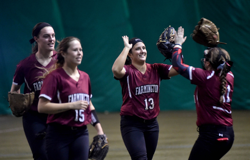 University of Maine Farmington center fielder Kiana Thompson (13) celebrates with teammates after beating the University of Maine at Presque Isle on Saturday at the Sport Dome in Topsham.