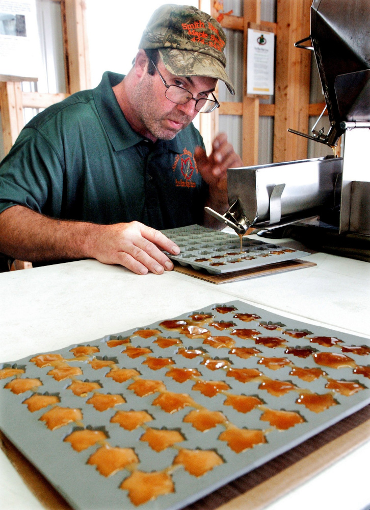 SKOWHEGAN,  ME-  August 14: James Smith lll of Smith Brothers Maple in Skowhegan fills trays with maple syrup to make maple candy inside the new Maple House exhibit building at the Skowhegan Fairgrounds on Sunday, August 14, 2016.  (Photo by David Leaming/Staff Photographer)