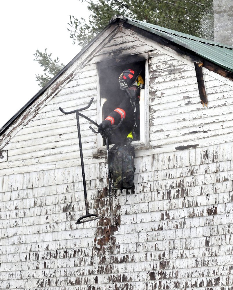 A firefighter throws burned items out a second-story window where fire destroyed a home Friday on Barker Road in Troy.