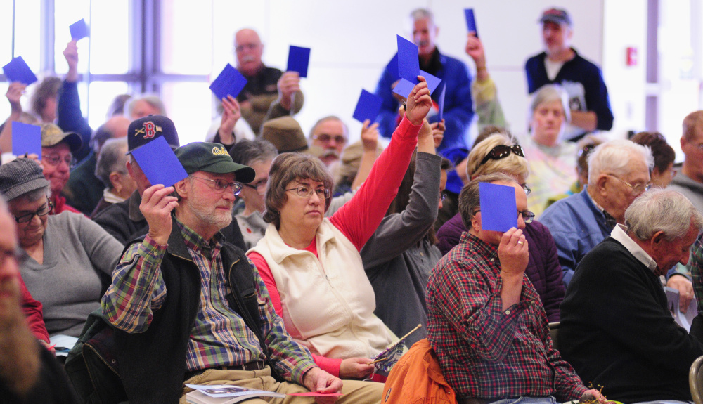 "Residents hold up blue cards to vote ""yes"" on a warrant item Saturday during the China Town Meeting in the China Middle School gymnasium."