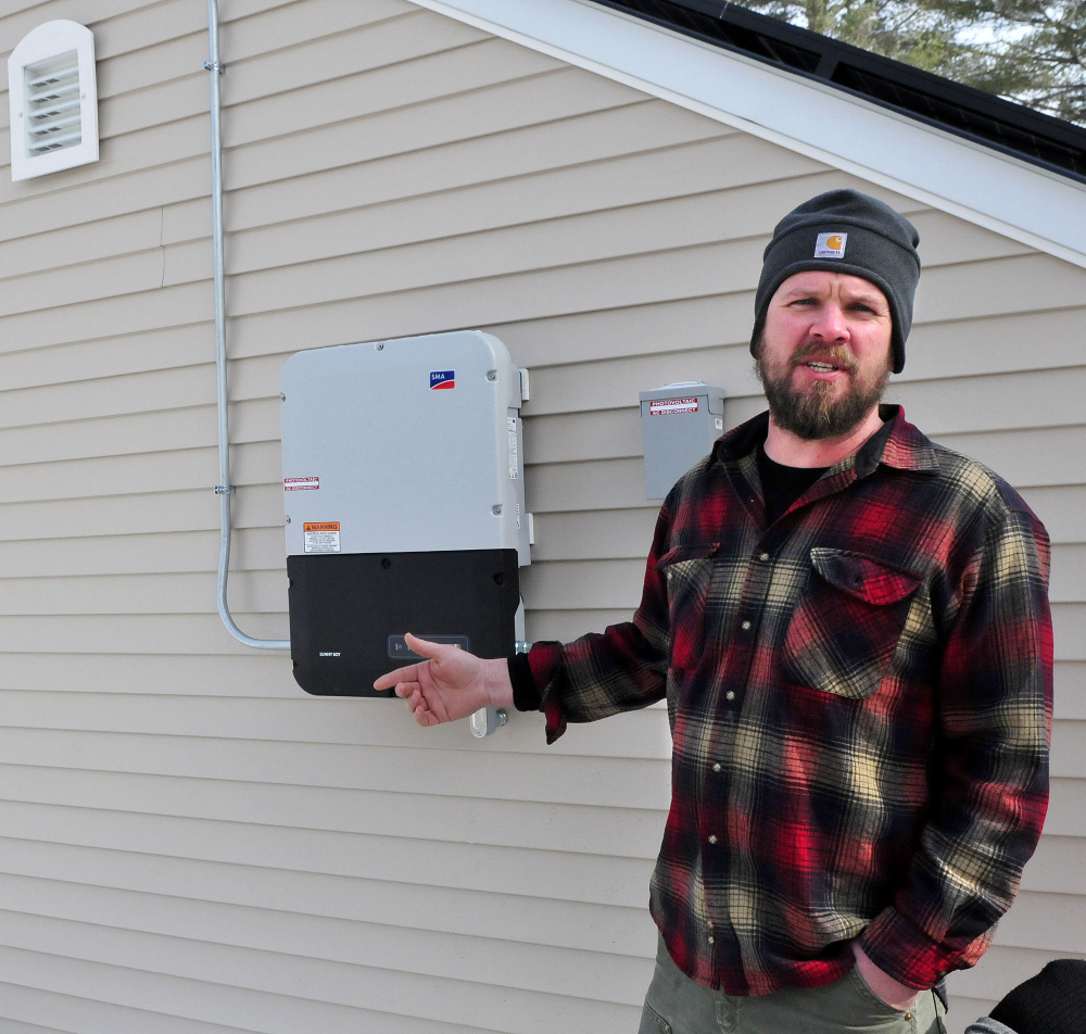 Matt Wagner of Insource Renewables in Pittsfield explains the process of an inverter that converts direct current energy to alternating current energy on a Backyard Buildings shed with solar panels in Unity on Wednesday.