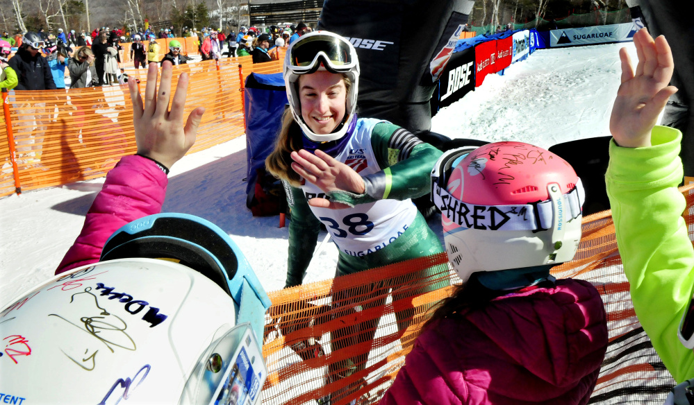 Carrabassett Valley Academy graduate Amelia Rowland signs autographs and gives high- fives to fans after competing in the second run of the women's slalom races during the U.S. Alpine Championships on Sunday at Sugarloaf.