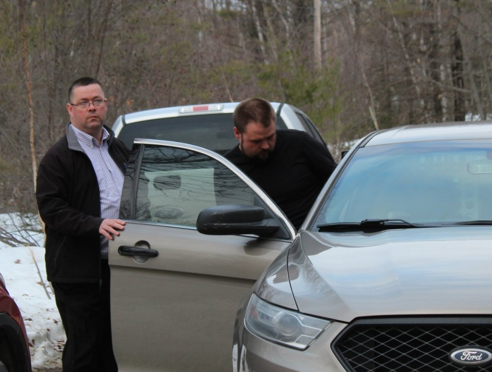 State police Sgt. Christopher Tupper puts Jared Moody into a cruiser Wednesday after Moody's arrest on a child pornography charge.