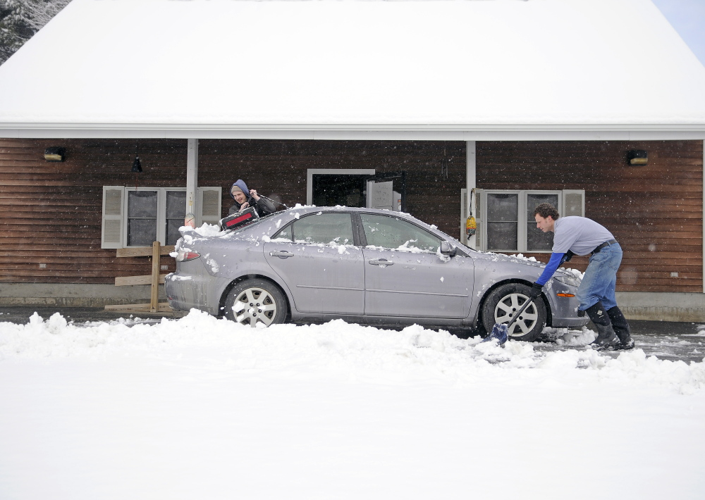 Justin Underwood, right, and Michael Giroux dig out from a snowstorm on April 9, 2015, at Underwood's business, Hallowell Seafood and Produce. An April Fool's Day storm is forecast to blanket the region Saturday.
