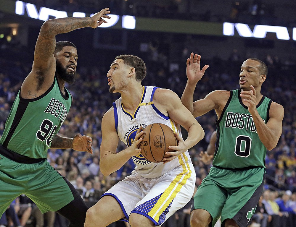 "The Celtics' Amir Johnson, left, and Avery Bradley guard the Warriors' Klay Thompson in the first half of  Wednesday night's game  in Oakland, Calif. ""They did a good job of guarding the 3,"" Thompson said after the game. ""Teams know we can kill them from 3."""