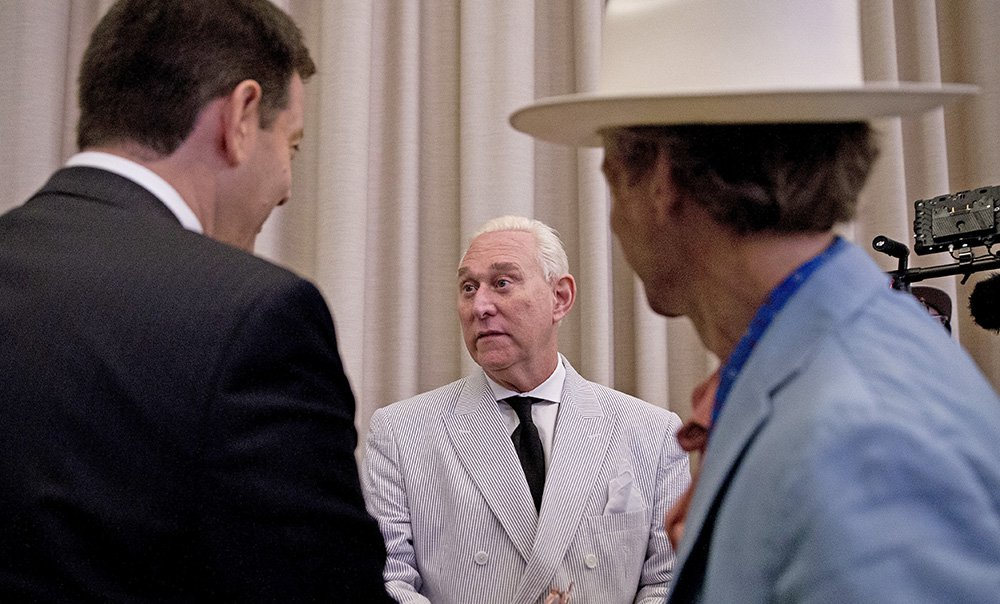 "Roger Stone, center, an adviser to Donald Trump, speaks to reporters in New York. He says he's retained two attorneys to explore whether he can compel the government to ""either charge me or admit they have no case whatsoever."""