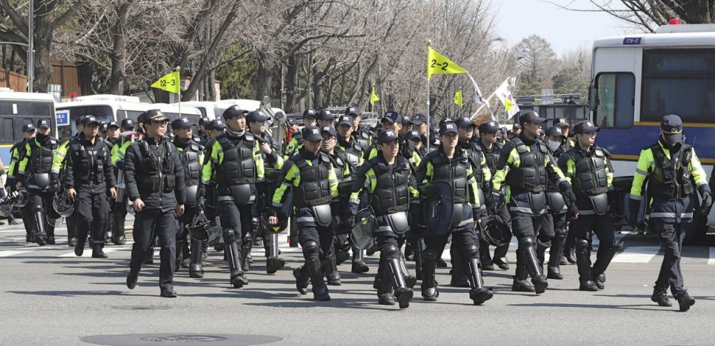 Police officers move near the presidential Blue House in Seoul, South Korea, Friday. South Korea's Constitutional Court formally removed President Park Geun-hye from office over a corruption scandal that has plunged the country into political turmoil and worsened an already-serious national divide.