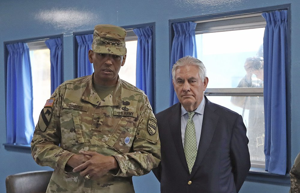 Secretary of State Rex Tillerson meets with U.S. Gen. Vincent K. Brooks, commander of the United Nations Command, Combined Forces Command and United States Forces Korea, last Friday in the village of Panmunjom, which has separated the two Koreas since the Korean War. In the background, a North Korean soldier takes a photograph through the window.