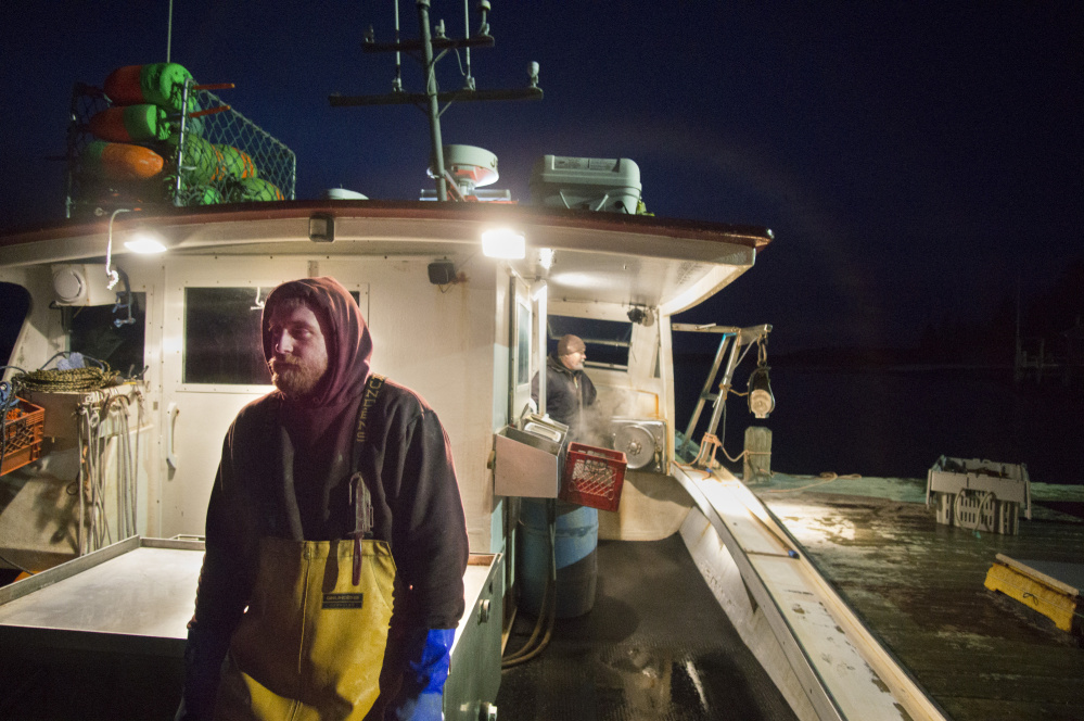 Joshua Kane, foreground, and Mark Pinkham offload lobster while docked at Cranberry Isles Fishermen's Co-Op on Little Cranberry Island. Kane, a 32-year-old lobster-fishing apprentice, is a former opioid addict who encourages other fishermen to seek treatment and talks openly about his own addictions. Staff photo by Gregory Rec