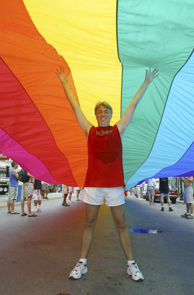 In 2003, Gilbert Baker stands in Key West, Fla., under a 1¼-mile-long rainbow flag that stretched across the island city from the Atlantic Ocean to the Straits of Florida.