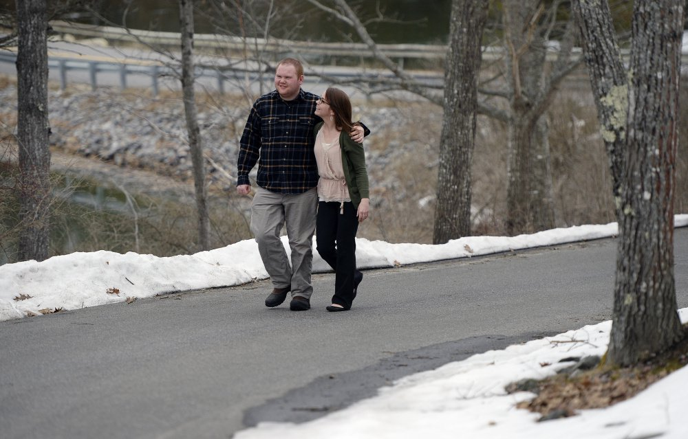 Kelsey Dunn and her brother Silas Gingrow walk near Gingrow's group home in Bath. Dunn works in human resources for the Independence Association, which runs group homes in the Brunswick area. Low MaineCare reimbursement rates have made it a nightmare for the homes to find workers, Dunn says.
