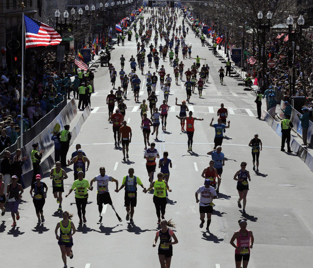 Runners approach the finish line of the 120th Boston Marathon on April 18, 2016, in Boston. Organizers of the 2017 race said the April 17 event will pump more than $192 million into the local economy, including $30 million for dozens of charities.