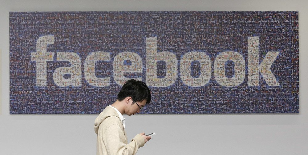 A man walks past a Facebook sign in an office on the Facebook campus in Menlo Park, Calif. Facebook announced Thursday it is launching a tool to help users spot false news articles on the site. The tool will be available to users in 14 countries, including the United States.