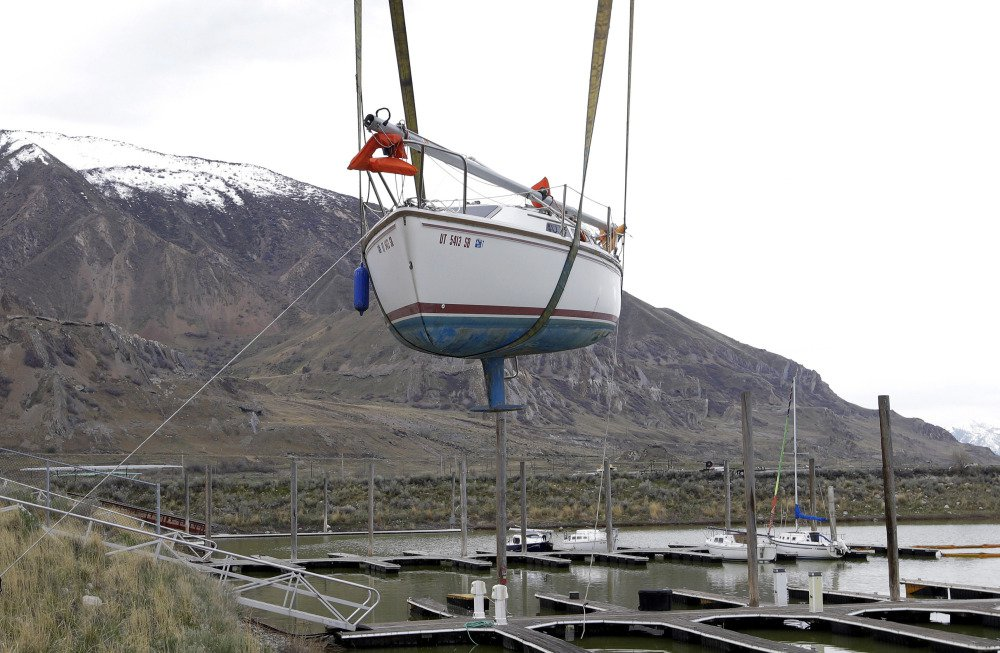 A beached sailboat is hoisted into Utah's Great Salt Lake on Thursday, about 20 miles west of Salt Lake City.