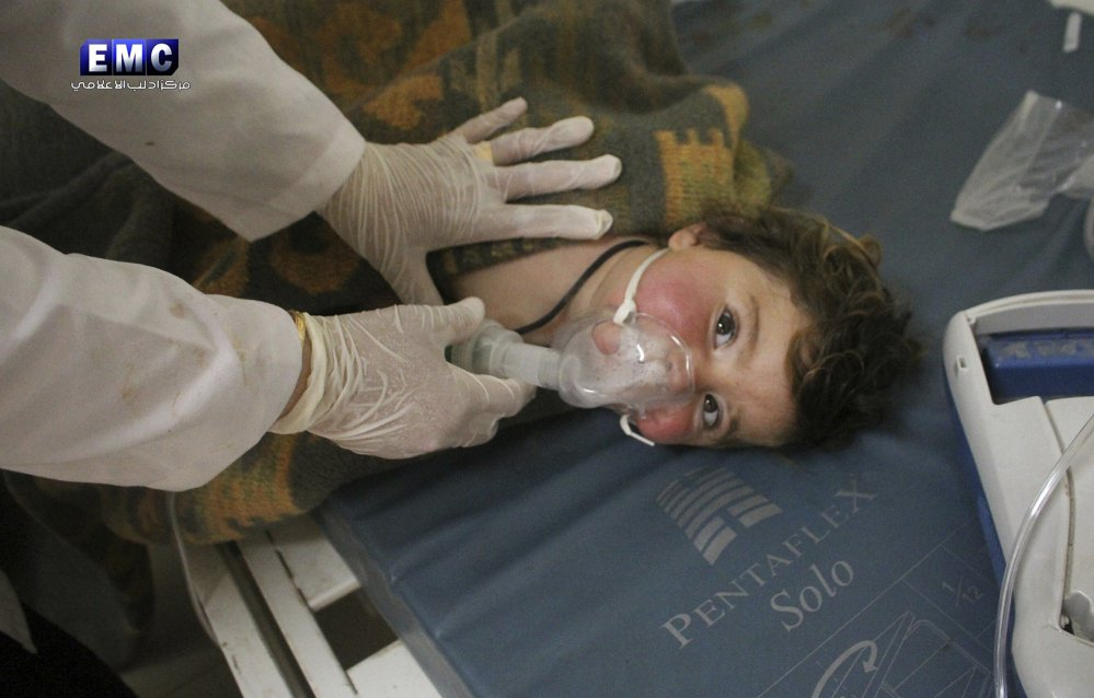 In a photo provided Tuesday by the Syrian anti-government activist group Edlib Media Center, a Syrian doctor treats a child in Khan Sheikhoun, Syria.