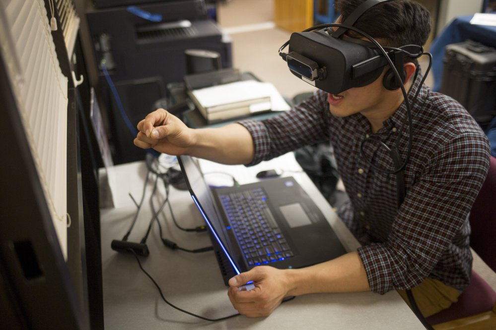 "Ryan Hoang, a first-year medical student at UNE, experiences how just grasping a pencil can be challenging when you're suffering from macular degeneration, courtesy of virtual reality software. ""It lets you experience the reality of having no control,"" Hoang said."