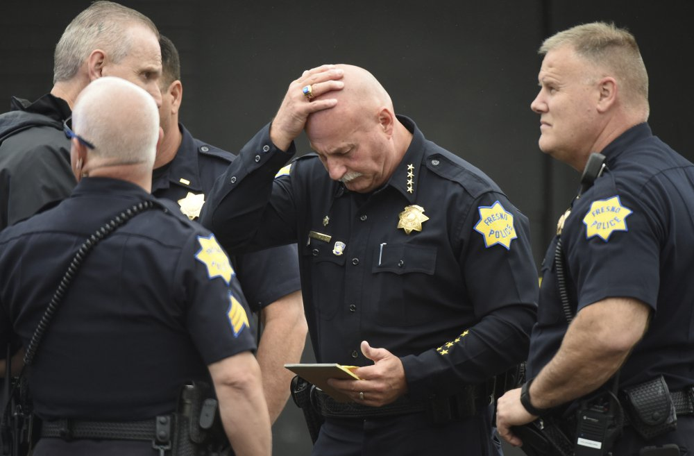 Fresno Police Chief Jerry Dyer reviews notes about the triple fatal shooting before addressing the media Tuesday in Fresno, Calif.