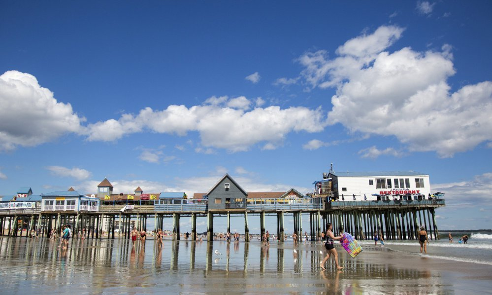 Beachgoers walk by the Old Orchard Beach Pier last summer. This popular tourist destination for generations of Canadians doesn't appear to be suffering from what industry experts predicted would be a