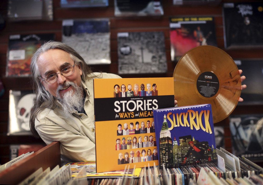 "Chris Brown poses with an orange vinyl recording of ""Stories for Ways and Means"" and Slick Rick's ""The Great Adventures of Slick Rick,"" a 7-inch single packaged in a board book, at Bull Moose Music in Portland on Friday. Brown, a Bull Moose employee, hatched the idea for Record Store Day that started with 200 stores 10 years ago. About 1,600 record stores are expected to participate on Saturday."