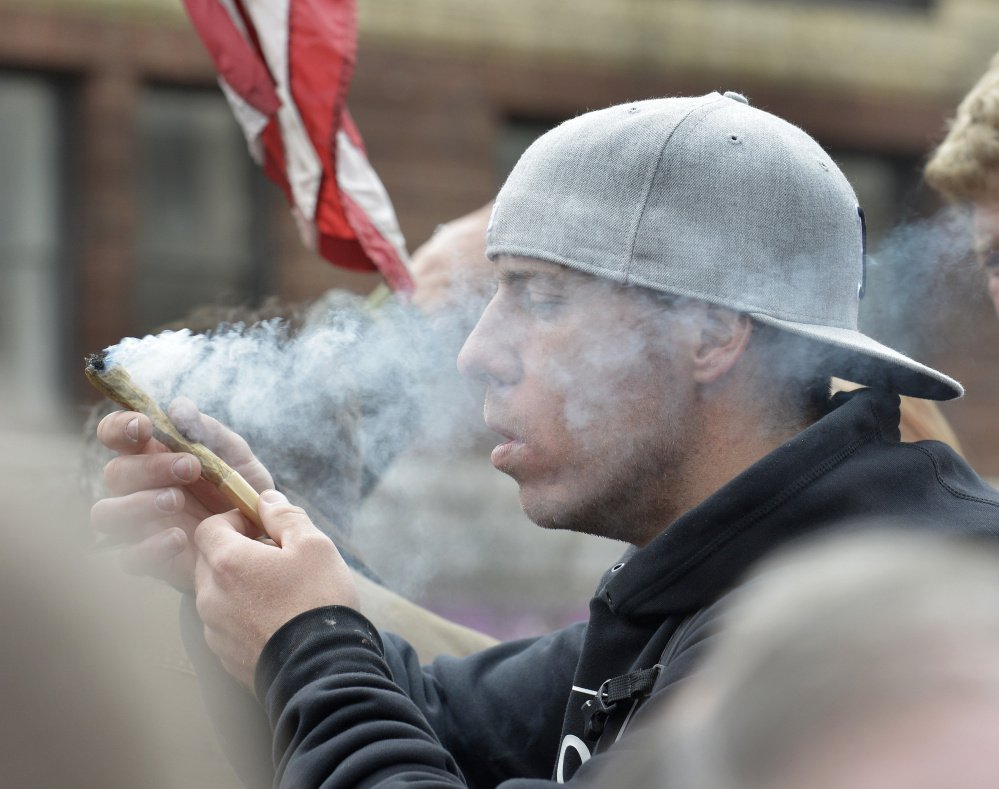 ABOVE: Justin Adgateo of Boston partakes of a monstrous 8-gram joint that was making its way through the crowd that gathered Thursday around marijuana advocate and writer Crash Barry, who was giving away free samples in Monument Square.
