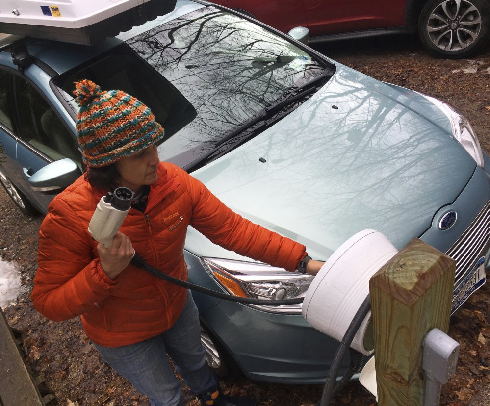 "Sunita Halasz shows how she charges her electric car at her home in Saranac Lake, N.Y. Halasz has tips for ""driving electric"" along lonely New York Adirondack Mountains roads."