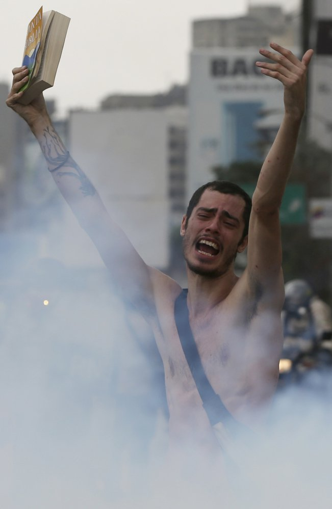 A protester holds a bible in a cloud of tear gas during a march in Caracas, Venezuela, on Thursday.