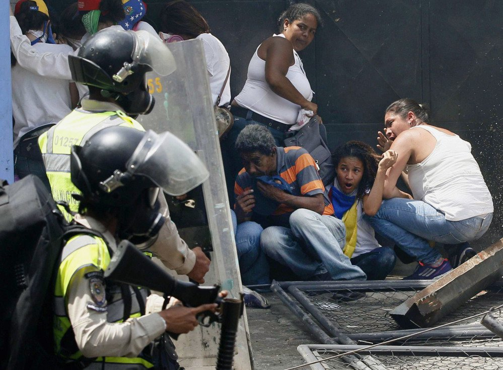 Anti-government demonstrators take cover from advancing police officers during protests in Caracas, Venezuela, Wednesday.