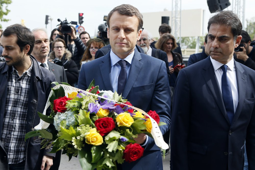 Presidential candidate Emmanuel Macron, center, next to Mourad Franck Papazian, co-president of France's Armenian Organizations Coordination Council, prepares to lay a wreath marking the 102nd anniversary of the slaying of Armenians by Ottoman Turks.