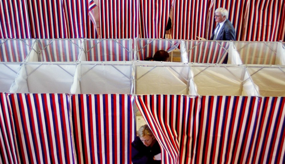 Voters make their way in and out of voting booths at Kennebunk Town Hall on Election Day in 2002.
