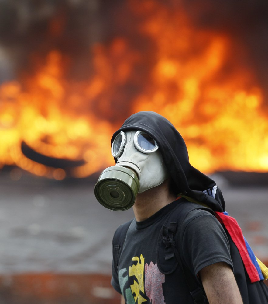 An anti-government activist standing in front of burning barricade is one of thousands protesting in Caracas, Venezuela, on Monday.