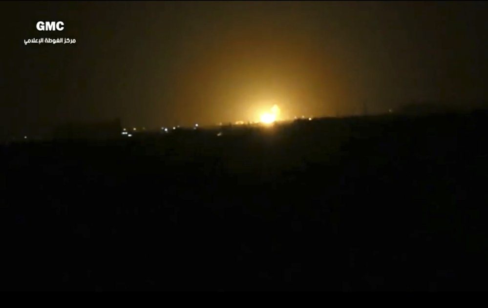 This image from video provided by the Syrian anti-government activist group Ghouta Media Center, which has been authenticated based on its contents and other AP reporting, shows flames rising after an explosion near an airport west of Damascus, Syria, on Thursday.