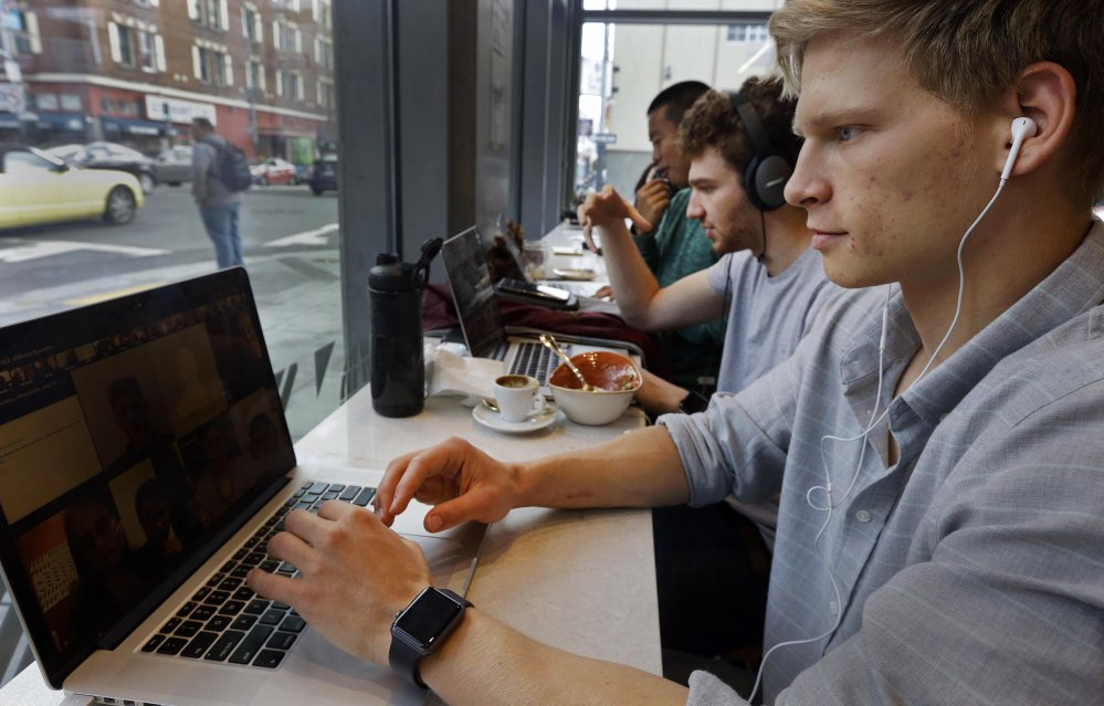Connor Mitchell, right, works on a computer at a cafe in San Francisco. With college costs rising steadily and with more courses available free online, some observers are beginning to question the need for traditional college.