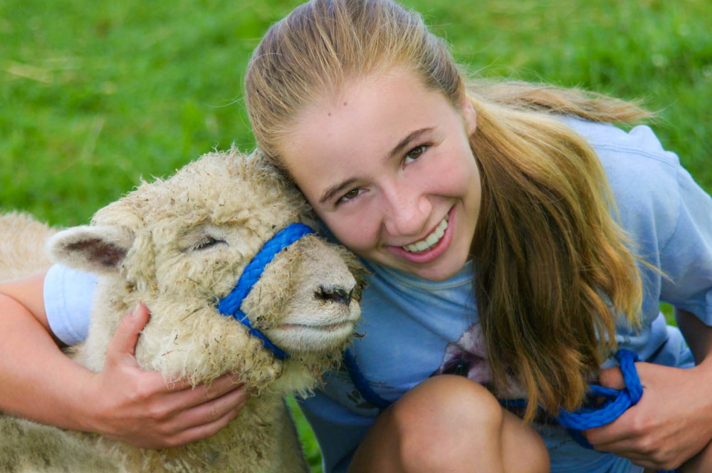 "Cassidy Charette with her ""adopted"" sheep Erwin at Hart-to-Hart Farm Camp in 2012. The Albion Farm will host its first ShineOnCass Easter Egg Hunt Sunday, April 9. Families are asked to bring pet items to be donated to the Waterville Area Humane Society in Charette's honor."