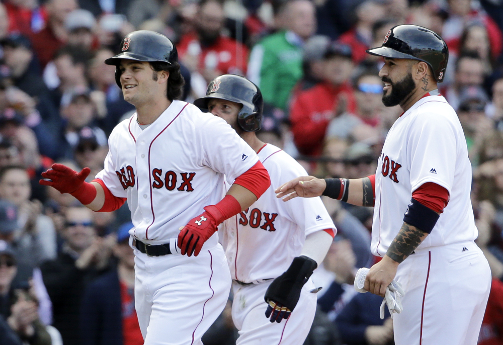 Boston Red Sox left fielder Andrew Benintendi, left, celebrates his three-run homer with teammates Dustin Pedroia, partially hidden, and Sandy Leon, right, in the fifth inning Monday against the Pirates in Boston.