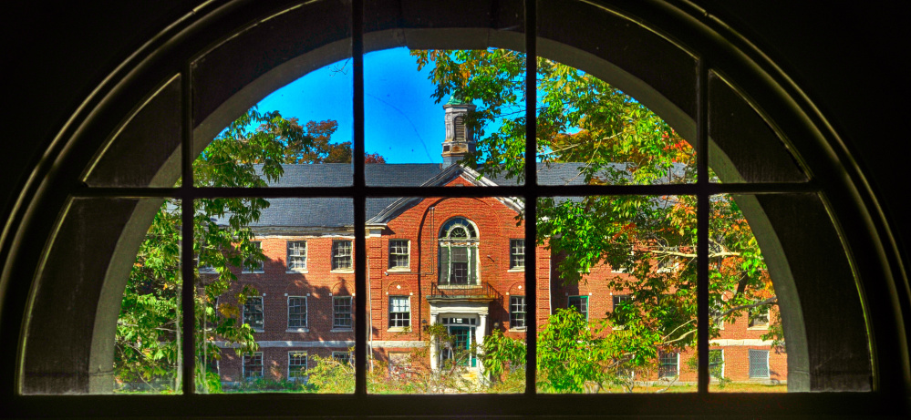 The Stevens Building is framed in a window of the Central Building during a tour on Oct. 7, 2016, at Stevens Commons in Hallowell.