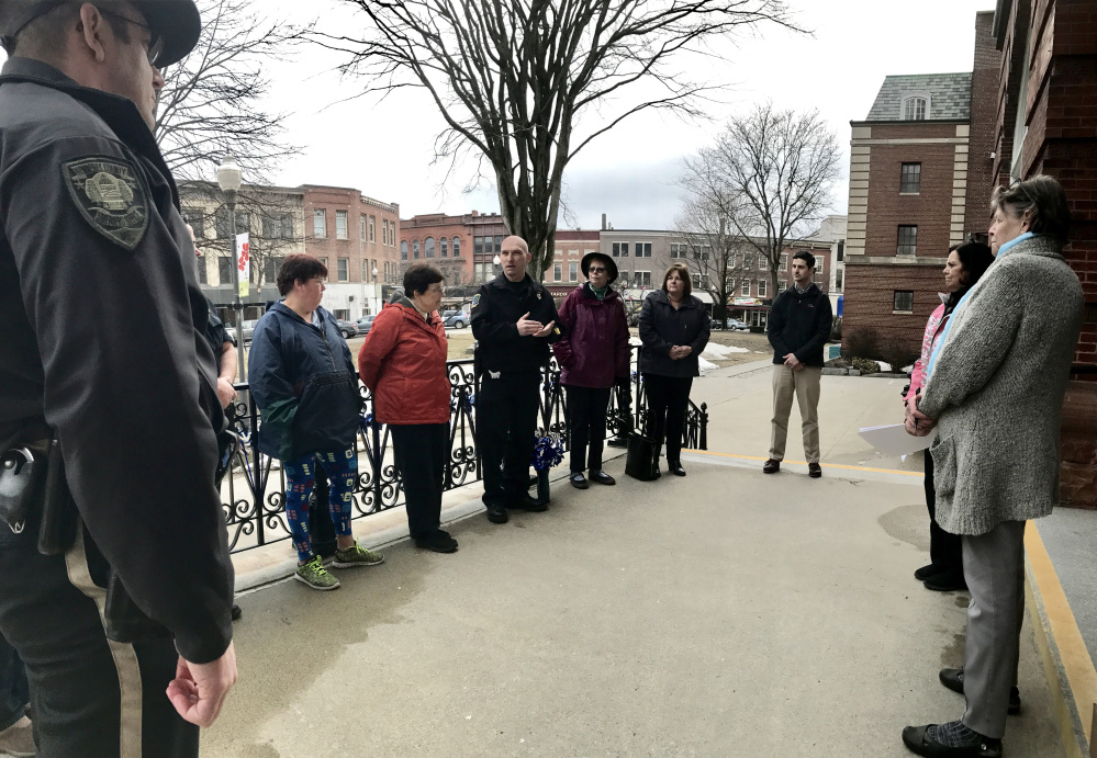 Bill Bonney, deputy chief of Waterville Police, center, speaks to about a dozen people who turned out Wednesday evening on the steps of Waterville City Hall to mark Child Abuse & Neglect Prevention Month.
