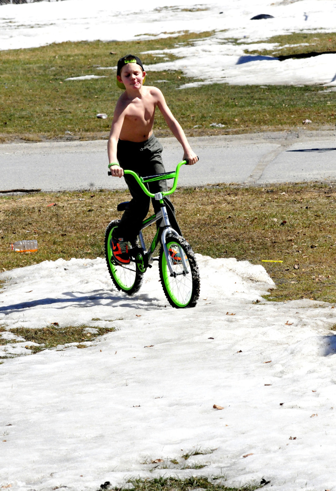 "It was warm enough on Sunday for Camren Foster to ride his bike without a shirt on in Waterville, but he soon found that riding through snow is not so easy. Asked how he liked the spring weather, Foster said, ""Good, no, perfect."""