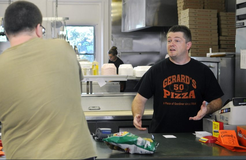 Gerard's Pizza proprietor Jeff McCormick speaks with customer Ben Tracy, of Gardiner, on Aug. 10, 2015, at the counter of the Gardiner restaurant. Gerard's opened that day after closing because of a fire on July 16 in neighboring buildings. Jeff McCormick died Saturday at the age of 43.