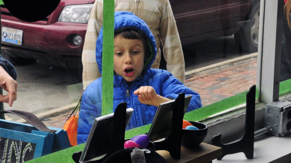 Victor Ilie, of Hallowell, counts eggs in the window of Niche, Inc. during the downtown scavenger hunt last year in Gardiner.